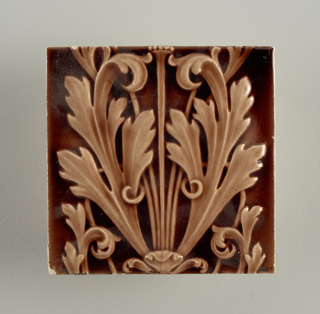 """Square molded tile of white clay; reversed imprinted with seventeen horizontal bars alternately imprinted and embossed with inscription: """"BF. AT. CO. L. and Lyre figures. Beaver Falls, PA"""". Tile face decorated with sections of acanthus fronds as part of a continuous vertical panel. Aubergine crackle glaze."""