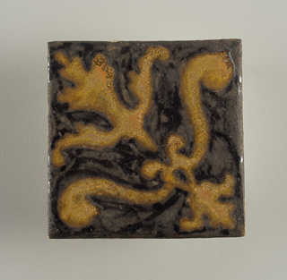 Square molded tile of brown earthenware; no inscription on reverse; tile face has stylized lily set above a bracket of two plumes; design arranged diagonally; ground matte black glaze, transparent crackle glaze on figure.