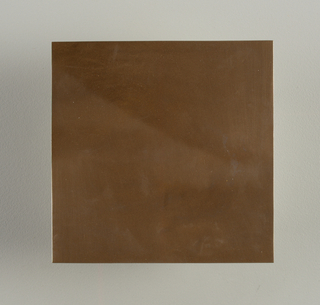 Square flat molded tile. Surface with metallic bronze finish; underglazed on reverse.