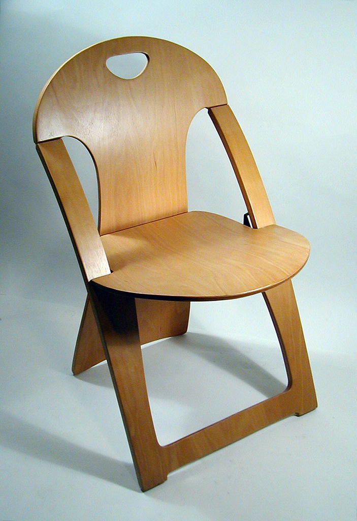 Two piece molded plywood chair with natural, symmetrical lines and a static tension system.  Pliable material (wood) is molded into the form of a chair without hinges.  Back support is punctured slightly at top for easy hand-transport.