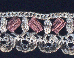 Decorative crochet band in pink and white with scalloped edge.