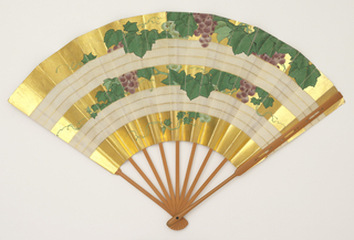 Pleated fan. Gilded paper leaf hand-painted with grape vines, interrupted by two bands of white stripes with fine, swirling lines. Bamboo sticks. Silk-covered cardboard case of yellow and royal blue silk satin embroidered with couched gold metallic yarns; blue and white braided edging, red ribbon.