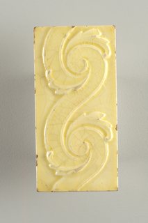 "Rectangular molded tile of white clay, reverse stamp with framed double bars with central inscription: ""Trent"". Tile face shows part of scrolling arabesque glaze yellow crackle glaze."