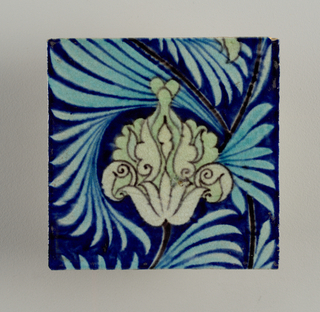 "Square tile of reddish clay with grog added. On royal blue ground a conventionalized flower in pale green outlined with black and turquoise leaves. Part of large design. Impressed mark: Tudor rose surmounted by ""Sand's End Pottery Fulham Wm. De Morgan & co."""