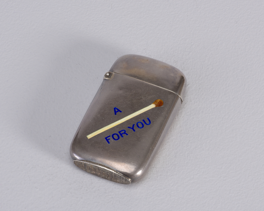 "Rectangular, rounded sides and corners, featuring word/picture rebus, inscribed in blue enamel ""A [Match] For You"", a matchstick with red tip substituted for the word ""Match"". Reverse inscribed ""Addie to James"". Lid hinged on upper left. Striker on bottom"