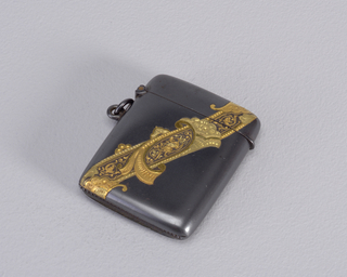 Rectangular, rounded sides and corners, body of gun metal with diagonal decorative gold band featuring scroll and fan-like motifs, as well as fine grotesque-like ornament running down band's center with griffin and other animal forms. Reverse undecorated. Links attached beneath hinge. Lid hinged on side, thumb catch opposite. Striker in recessed groove on bottom.