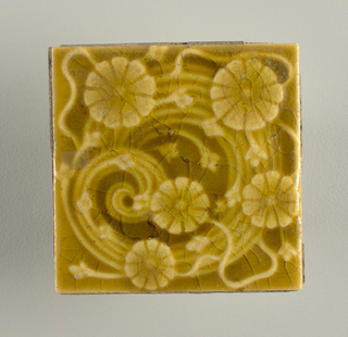 "Molded square tile of white clay, reverse has inscription in frame of double lines: ""Trent Tile/ Trenton, N.J. / U.S.A."". Tile front series of daisy-like flowers scattered on a wide, four-stem coil interwoven with a loose vine figure."