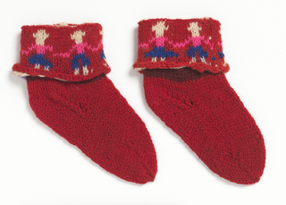 Pair of child's knitted socks in bright red wool; ankle length with turned cuff; design of children's figures, hand-in-hand, in blue, pink and white.