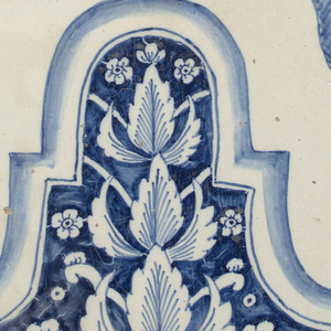 Four blue and white glazed earthenware tiles forming pattern of floral swags and tassels hanging from valance.