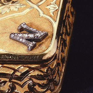 """A gold box with a personalized lid. The letter """"N"""" in each of the lid's corners in diamonds. The center of the lid is decorated with another larger letter """"N"""" in diamonds with a diamond crown above the letter. Along the sides of the box there is an abstract design carved in gold."""