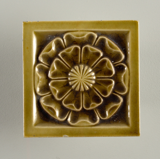 "Square molded tile made of white clay, impressed and inscription: ""J. & J.G. Low, Patent Art Tile Works, Chelsea Mass. U.S.A., copyright 1881 by J. & J.G. Low"". Tile face is decorated with a stylized flower having two rows of concentric pedals, center rosette, framed in plain border; glazed dark teal blue."