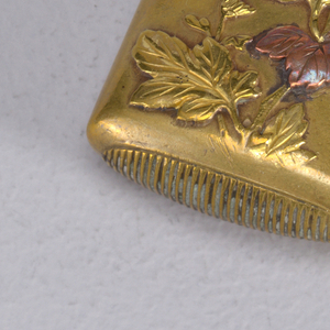 Oblong, curved sides and corners, featuring raised ornament of chrysanthemum flowers and foliage, some leaves highlighted with silver and copper, a single butterfly on lid, variation of floral ornament on reverse. Lid hinged on side. Oval shaped striker on bottom.