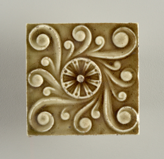Square, molded tile of white clay; reverse has a waffle pattern in low relief; tile face is decorated with a central rosette figure surrounded by irregular, acanthus-like figure.