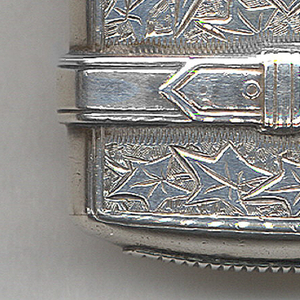 """Rectangular, curved sides, top and bottom, resembling a valise with leather straps that wrap from front to back, buckles on each strap on both sides, front features incised decoration of leaf motif, shield reserve at center inscribed """"From [illegible monogram]"""", part just above strap opens as lid, hinged on side, thumb catch opposite, top of lid inscribed """"A. Huttenback, 20th July, 1884."""" Same leaf motif with flowers at center incised on reverse. Striker on bottom."""