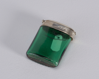 Rectangular, rounded sides and curved top, body made of transparant green glass, silver collar wrapped around upper edge, where it meets silver lid. Lid hinged on side, at point where it meets collar. Striker incised in glass in diamond pattern on bottom.