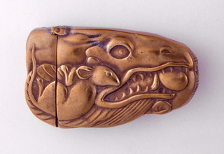 In the form of a dragon's head, pearl clasped in bared teeth, rodent hangs on to dragon's gills; reverse features rodent hanging upside down from dragon's mouth. Back of neck, hinged on top, opens as lid. Striker on front of snout.