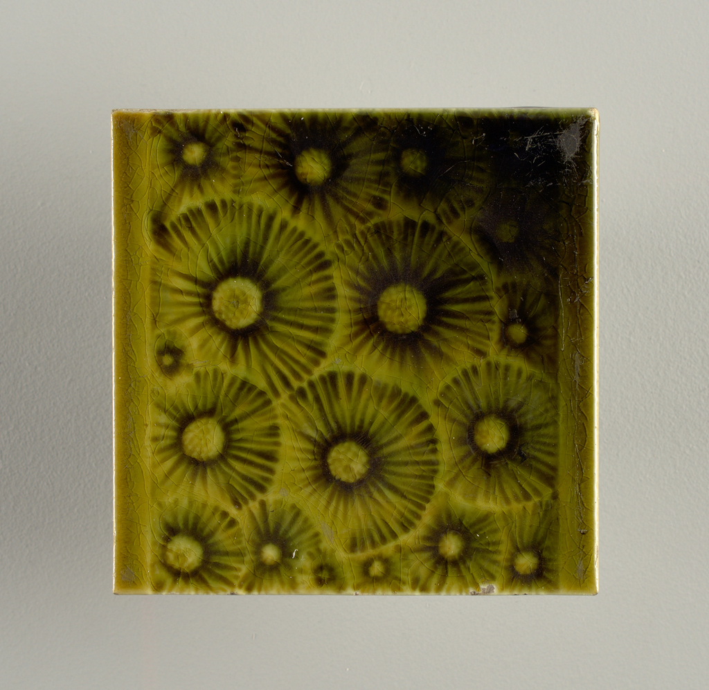 """Square, molded tile made of white clay, impressed and inscription: """"J. & J.G. Low, Patent Art Tile Works, Chelsea Mass. U.S.A., copyright 1881 by J. & J.G. Low"""". Face of tile has plain border top and bottom, all-over pattern of stylized dandelion flowers (gone to seed) painted yellow-green crackle glaze."""