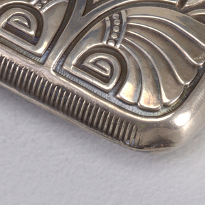 Rectangular, rounded corners, with relief decoration on lid of winged scarabs, stylized lotus blossoms, and other Egyptian motifs on body; plain reserve of irregular hexagonal shape, monogram incised in reverse reserve. Lid hinged on side. Striker on bottom.