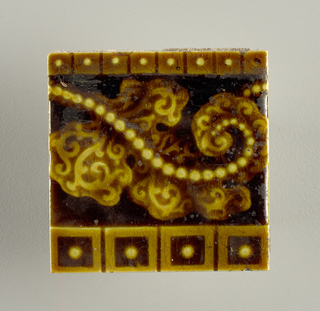 """Square, molded tile of white clay; reverse of tile has series of nine horizontal bars alternately raised and recessed with """"Trent"""" embossed on wither side of raised bar. Tile face ornamented with beaded leaf figure framed within horizontal bands of dot-centered blocks; glaze is molasses-brown crackle."""