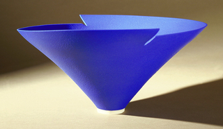 Blue ceramic bowl of inverted conical form with indented rim of opposing heights; narrow circular foot in white.
