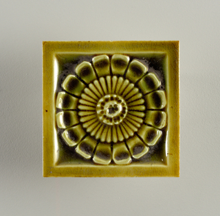 "Square molded tile made of white clay. Tile back has design of raised concentric circles framing inscription: ""J. & J.G. Low, Patent Art Tile Works, Chelsea Mass. U.S.A., copyright 1881 by J. & J.G. Low"". Face of tile has central rosette framed by plain narrow border. Tile is painted mustard-green crackle glaze."