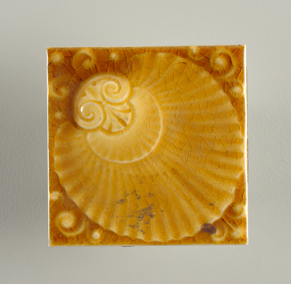 """Square molded tile made of white clay; reverse has seven horizontal bands alternately raised and impressed; inscribed on center band; """"A.E.T. Co. Ldt"""". Face of tile is decorated with ornate scallop shell placed diagonally across surface; """"pelta"""" figure at shell foot; honey-colored crackle glaze."""