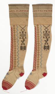 """Stockings with horizontal bands of decoration at the top. In one of the bands are the words """"Regalo de un triste preso,"""" which translates to """"Gift of a sad prisoner."""" The other stocking has a band with the name: """"Ana Maria Martinez."""" Just below are vertical bands with geometrical motifs in red, blue, light brown and black. Foot is white with a red heel and toe. Blue and red pattern on the instep."""