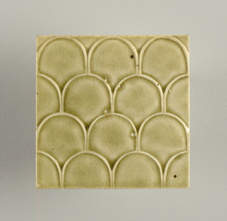 "Square molded tile of white clay, impressed on the back with inscription: ""J. & J.G. Low, Patent art Tile Works, Chelsea Mass. U.S.A., copyright 1881 by J. & J.G. Low"". Face of tile is stamped with imbricated scale pattern, glazed with a green crackle glaze."
