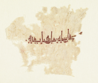 Arabic inscription embroidered in red silk on a natural linen ground. Translation: Bismillah ir-Rahman – In the name of God the Merciful.