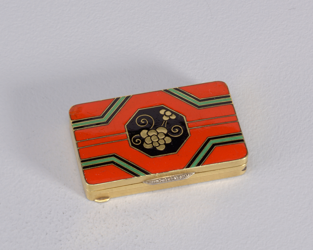 Rectangular, rounded corners, snuff-box type container with cloisenné enamel decoration. Lid features red-orange ground on which stylized gold flowers with delicate swirling stems are set in central, black enameled, octagonal reserve. Two narrow, parallel, gold bands extend from left and right sides of octagon, outward to box's edges. Bisecting each corner are angled, geometric green and black enameled bands. Thumb catch on lid inset with five small diamonds. Smaller, gold thumb brace situated on lower left corner of front side panel. All four side panels are reeded. Gold underside incised with pattern that mirrors overall geometric pattern of lid, without flower motif. Lid hinged on back panel. Striker inset on right side panel.