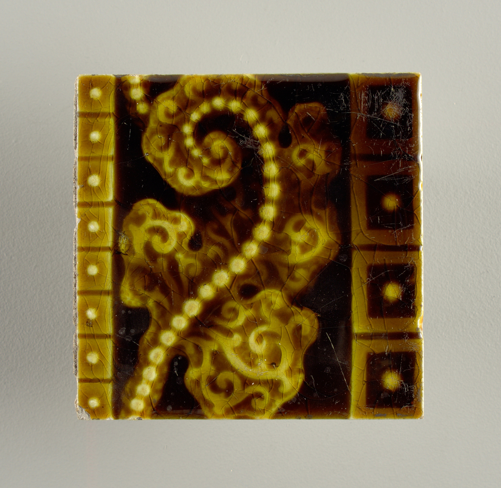 """Square, molded tile of white clay; the reverse of the tile has a series of nine horizontal bars alternately raised and recessed with """"Trent"""" embossed on wither side of a raised bar. Tile is ornamented with beaded leaf figures framed within horizontal bands of dot-centered blocks; molasses-brown crackle glaze."""