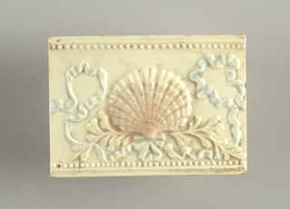 "Rectangular molded tile of white clay, reverse inscription in low relief: ""Old Bridge"". Face of tile has scallop shell set on pair of crossed boughs tied by ribbon bow whose ruffled ends frame the shell. Horizontal beaded borders. Underglaze blue, pink, yellow."