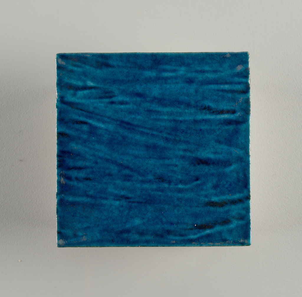 "Square tile or buff clay with grog added. Streaky brilliant peacock-blue colored glaze, crackled. Impressed mark: ""Dm 98"""
