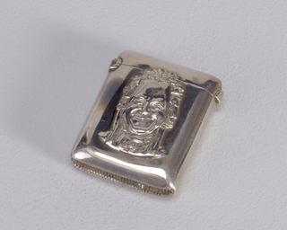 "Rectangle with blunt corners.  Plain silver surface with relief decoration in center a bust of grinning actor dressed as ""Charlie's Aunt""."