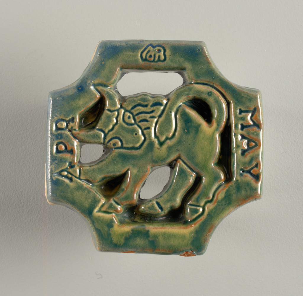 """Cross-like-shaped tile, depicting a bull in openwork. Left: """"APR"""" and right: """"MAY""""."""