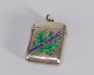 "Rectangular, with engraved thistles and foliage on body, enameled in pink and green.  A diagonally draped banner, inscribed ""DINNA FORGET"" in blue enamel, bisects the decoration. No decoration on lid or reverse. Link attached to top of lid. Lid hinged on left. Striker on bottom."