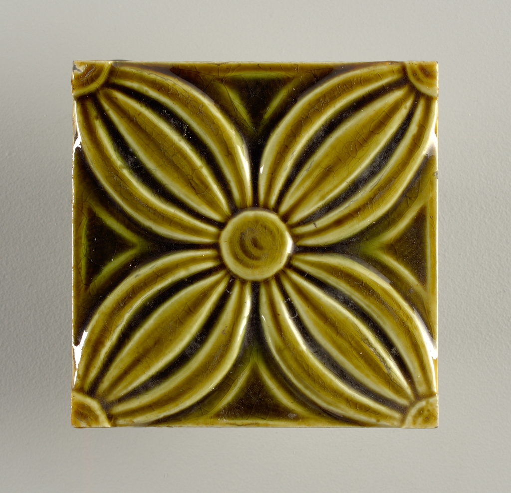 """Square, molded tile of white clay; reverse bears inscription in double line frame: """"J. & J.G. Low/ Patent Art Tile Works/ Chelsea, Mass. U.S.A. / copyright 1881 by J & J.G. Low"""". Face of tile is decorated with four petalled flower placed so that petals extend into corners; painted dark, green crackle glaze."""