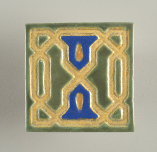 Square tile of rough yellow clay; face is cut with irregular geometric designs in the style of Islamic interlace; designs glazed matte green and blue, ground matte yellow; underglazed tile edges. No marks on reverse.