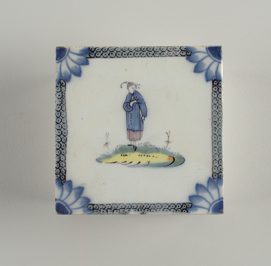 Square tile. Center reserved in white, with male figure in Chinese style, manganese and blue, standing on green and yellow mound. Blue border with double row of black circles and dots; flower quadrants at the corners.
