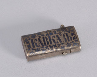 "A rectangle matchsafe in a dark metal with a black ivy pattern around the word ""KABKA3b"" A cyrilic spelling for Caucasus"