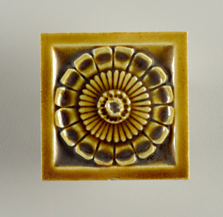 "Square, molded tile of white clay, reverse is embossed with an inscription framed in three concentric circles: J. & J.G. Low, Patent Art Tile Works, Chelsea Mass"" Face is decorated with a stylized rosette set in a plain, narrow frame; crackle glaze is mustard yellow."