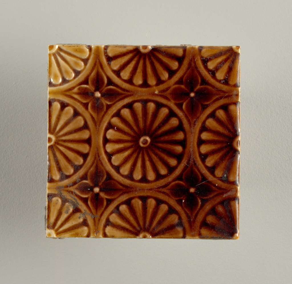 """Square molded tile made of white clay, impressed and inscription: """"J. & J.G. Low, Patent Art Tile Works, Chelsea Mass. U.S.A., copyright 1881 by J. & J.G. Low"""". Tile face has all-over design of daisies framed in plain circles separated by four-pedaled flower; cropped design indicate piece id part of larger tile scheme; dark brown crackle glaze."""