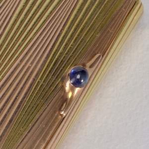 Rectangular form with design in Faberge style with pattern of alternating top to bottom two-tone gold triangles.  Onion shaped knob on top.  Blue stone on side.