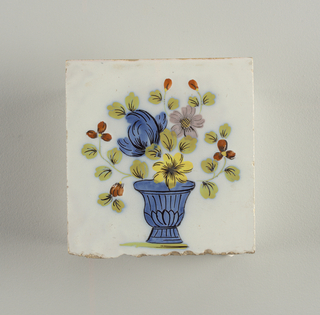 "Square tile. Decorated in ""Fazackerley colors"" on white ground.  Subject a blue vase with flowers in blue, yellow, manganese and brown; leaves sage green, with black veins."