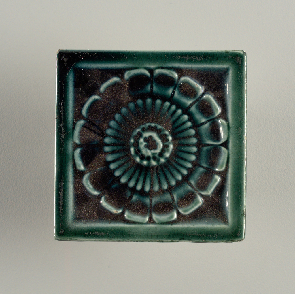 """Molded, square tile made of white clay, reverse bears impressed inscription set in a double-line frame: J. & J.G. Low, Patent art Tile Works, Chelsea Mass. U.S.A., copyright 1881 by J. & J.G. Low"""". Face is decorated with a simple rosette framed in a plain, narrow border; glazed a dark crackle green."""
