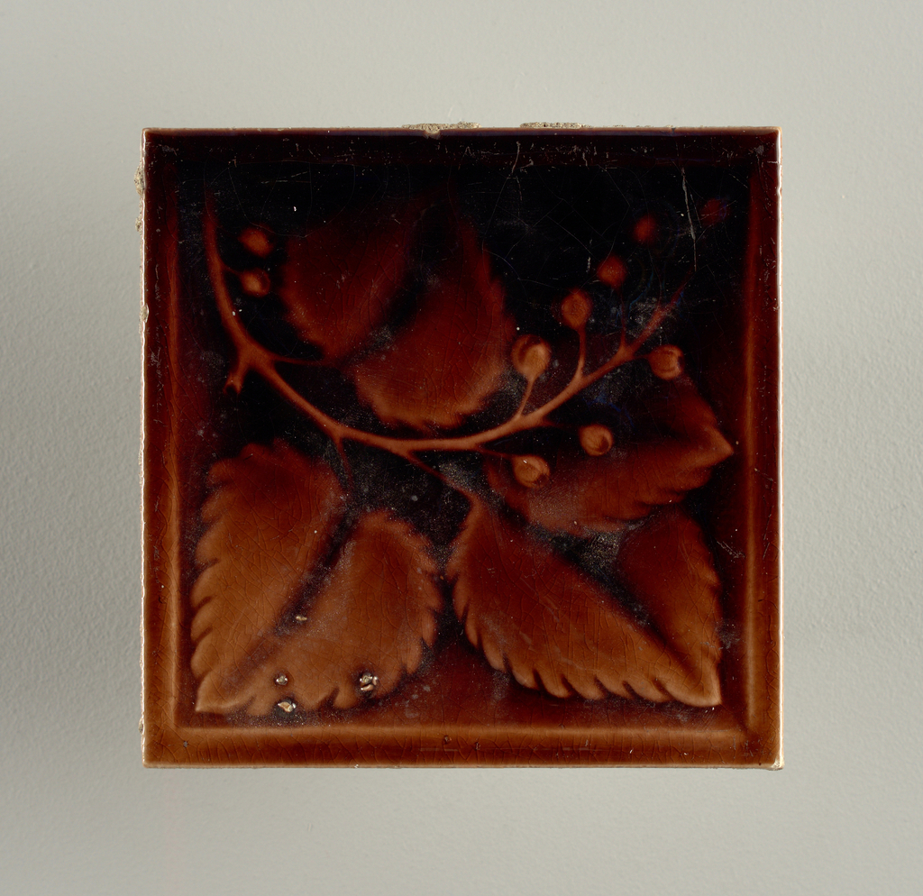 """Square molded tile made of white clay; back is stamped with two concentric circles, inner is inscribed: """"Hamilton Ohio"""" Tile face is decorated with a berry branch, glazed a deep brown."""