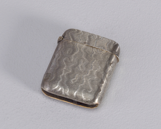 A silver square shaped matchsafe with rounded corners. The texture on the matchsafe references water with a wavy repetitive pattern.