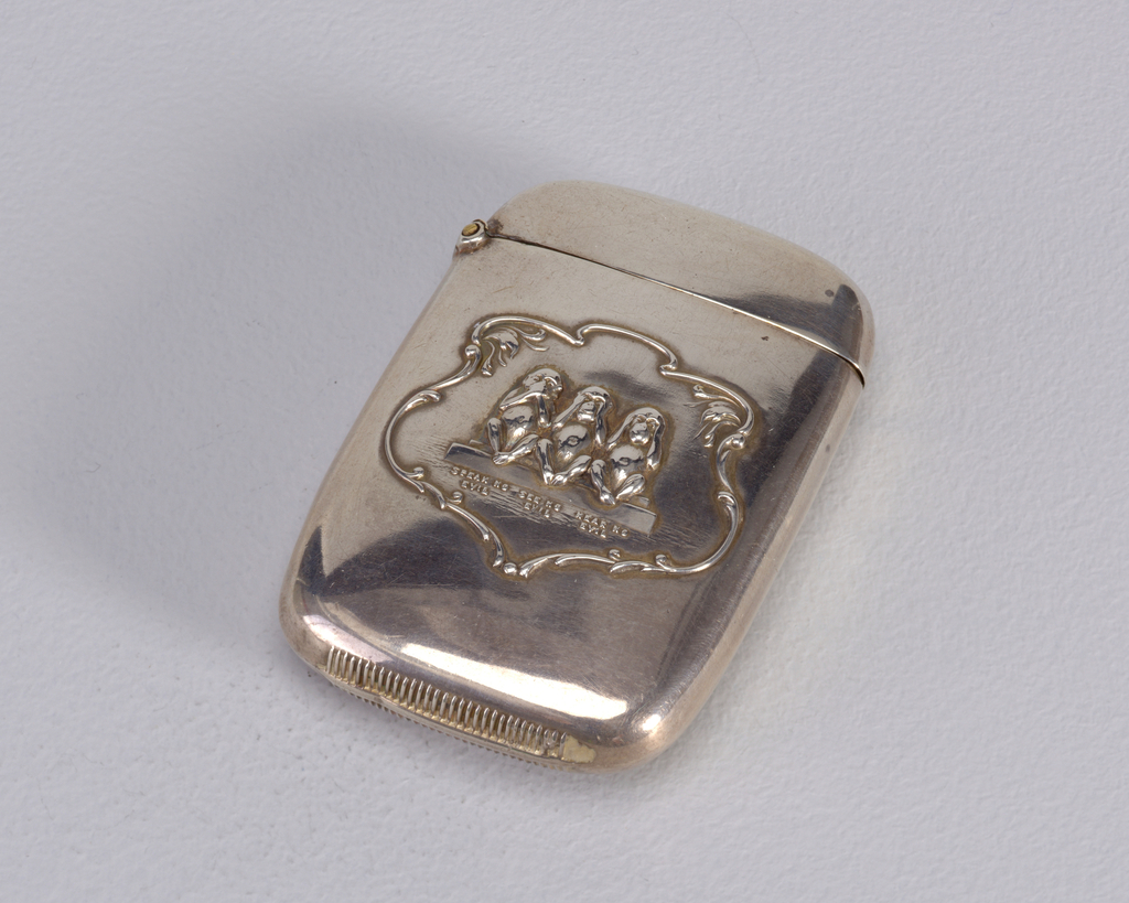 """Rectangular, rounded sides and corners, featuring raised decoration of 3 seated monkeys, with hands over mouth, ears, and eyes, inscribed beneath each respectively """"Speak No Evil"""", """"See No Evil"""", """"Hear No Evil"""", all framed by decorative cartouche. Lid hinged on side. Striker on bottom."""