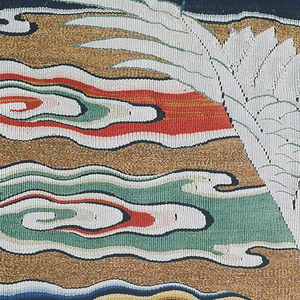 Most of a Ming dynasty First Rank square showing a pair of cranes with spread wings arched across a gold sky filled with brightly colored attenuated cloud streamers. Birds are white with gray and black lower wing feathers and throats, vermillion crests, and beak, feet and eye details in black and pale green. Cloud bands are white with shades of blue, pale green, yellow and vermillion on a gold metallic ground.