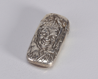 Oblong, rounded corners, featuring raised decoration of grinning court jester face in costume, he holds miniature jester head on a stick. Reverse inscribed with monogram J.C.Y. Lid hinged on side. Striker on bottom.